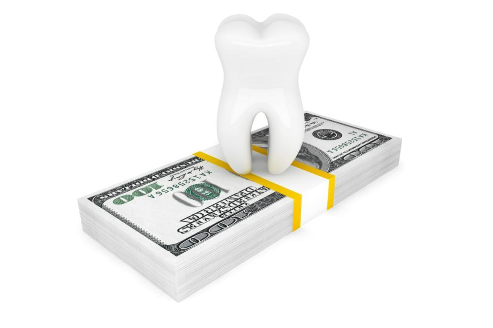 a tooth sits on a stack of dollar bills | affordable dentist springfield mo
