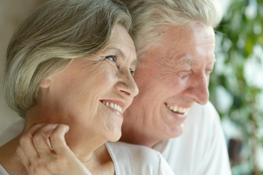 Happy elderly couple smiling wearing dental implants near 65804