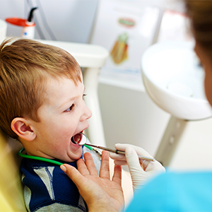 young boy getting his teeth checked by dentist
