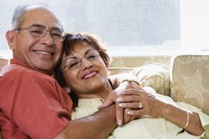 an older couple smiles on a couch | springfield mo emergency dentist
