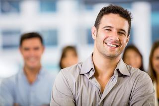 a man smiles with people smiling behind him | southeast springfield mo invisalign dentist