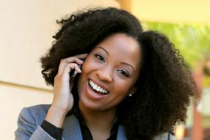 a woman smiled while talking on the phone | dental veneers in springfield mo