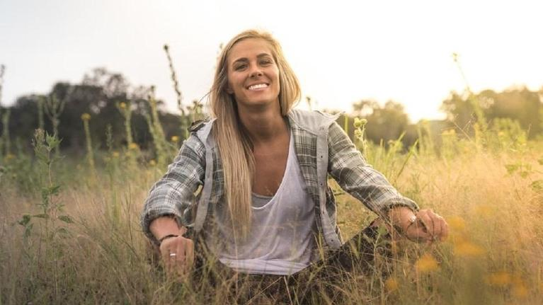 girl sitting in a field | Invisalign Springfield MO