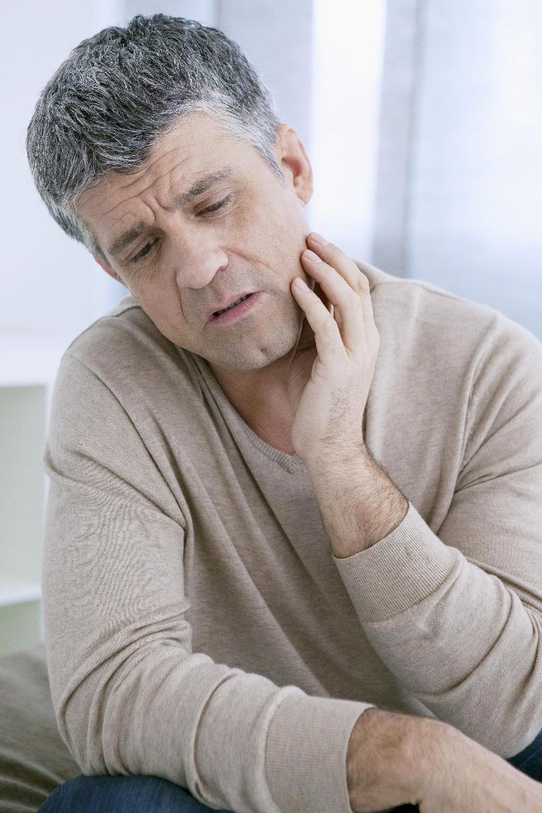 a man holds his hand up to his jaw in concern | emergency dentist springfield mo